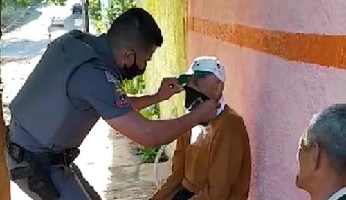 Policiais militares orientam idosos na colocação de máscaras de proteção